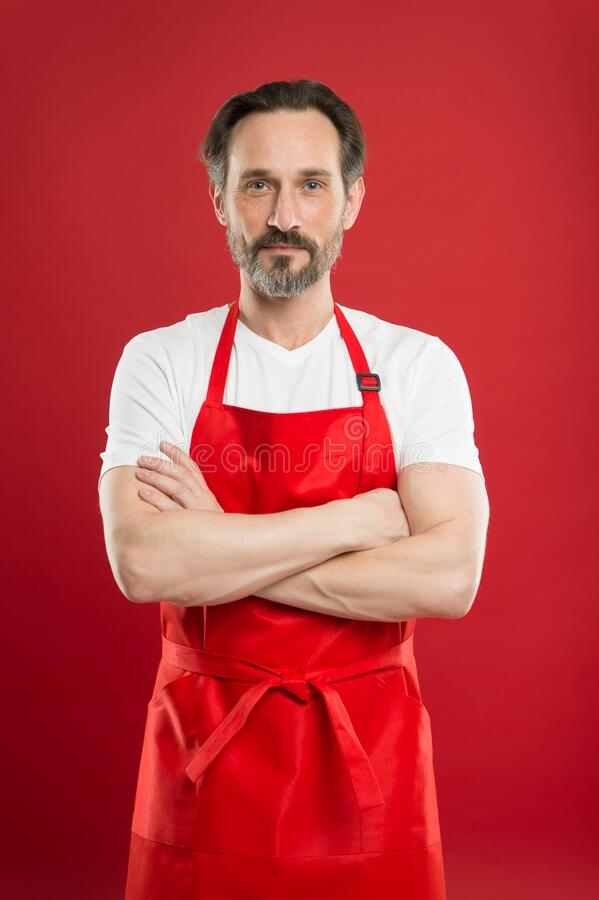 Confident in his culinary craft. Cook with beard and mustache wearing apron red background. Man mature cook posing stock photos