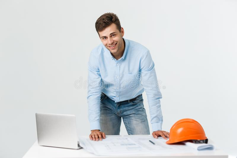 Confident in his new project. young engineer and architect man working on laptop and looking at camera with smile while stock images