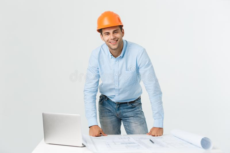 Confident in his new project. young engineer and architect man working on laptop and looking at camera with smile while stock photo