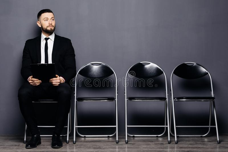 Confident job applicant reads resume while sitting on chair in row in office and waiting his turn on interview. Young guy wearing stock photo