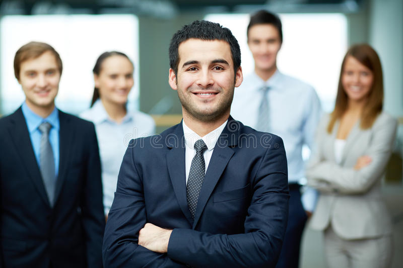 Confident leader. Group of friendly businesspeople with male leader in front royalty free stock images