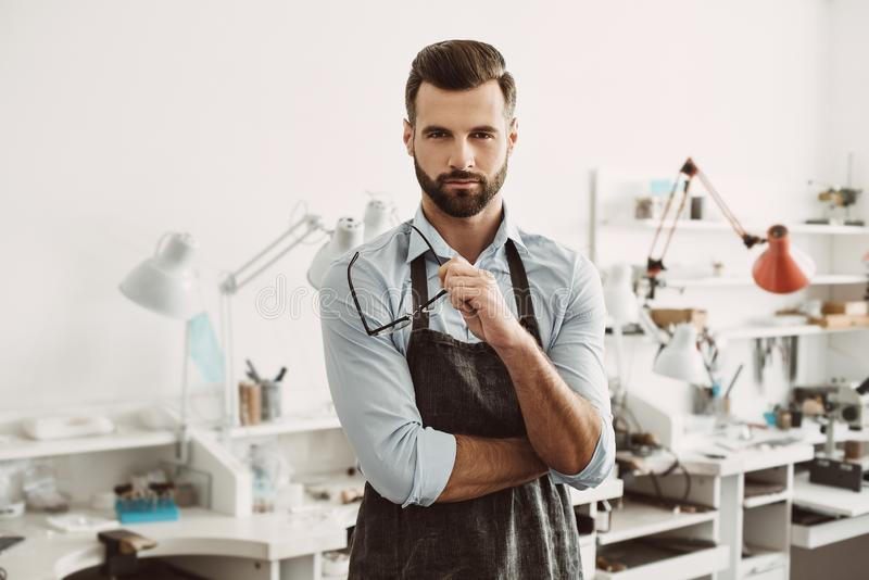 Confident leader. Portrait of confident male jeweler wearing apron and holding glasses stock image
