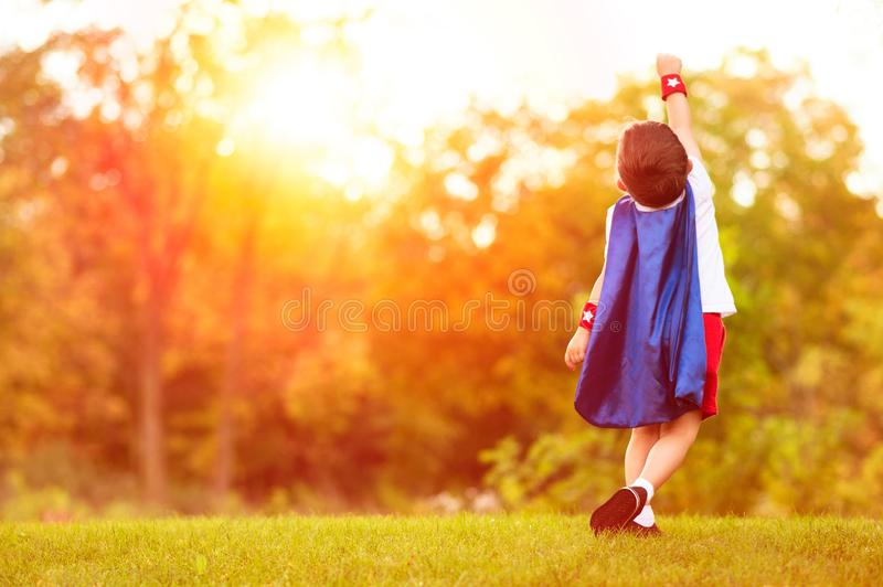 Confident little child boy plays superhero. Child with background of sunset sky. stock photography