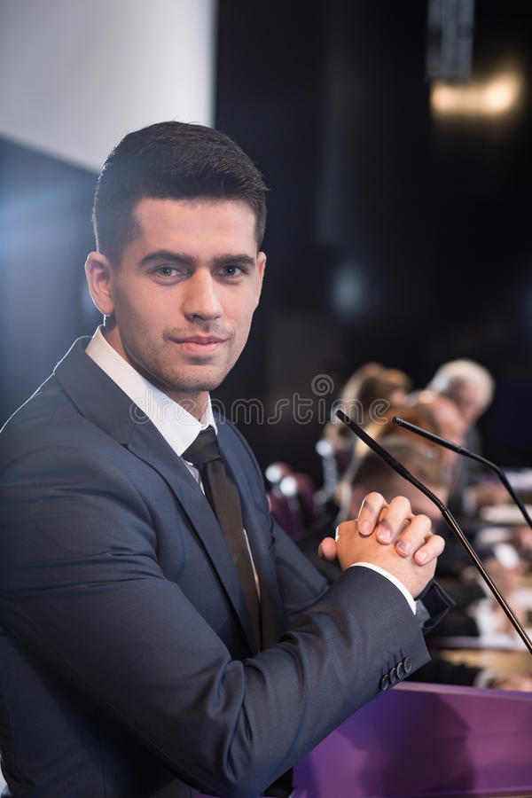Confident look of a talented young speaker. Portrait of a young professionally-looking man sitting at a conference table stock image