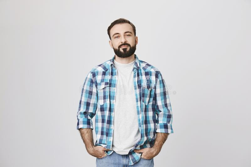 Confident-looking guy with moustache and beard, holding hands in pockets and looking at camera, over gray background royalty free stock photo