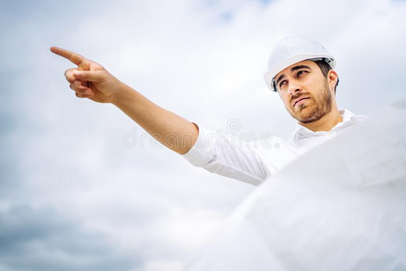 male architect working and pointing with finger on construction site royalty free stock image