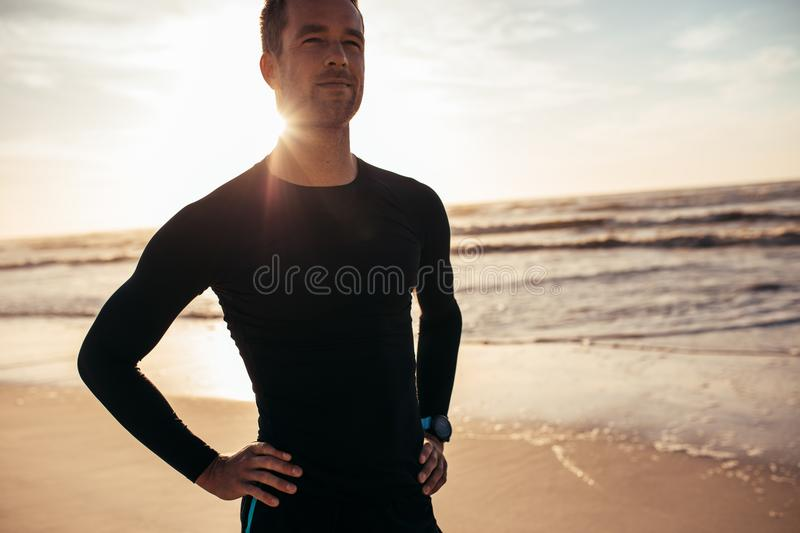 Confident male athlete standing on the beach stock photos