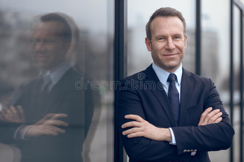 Confident male businessman leaning on window stock photography
