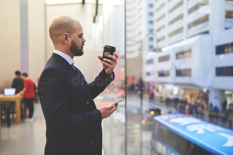 Confident male CEO with cell telephone in hands is resting after work day. Young man proud lawyer with mobile telephone in hand is watching on a cup take away stock image