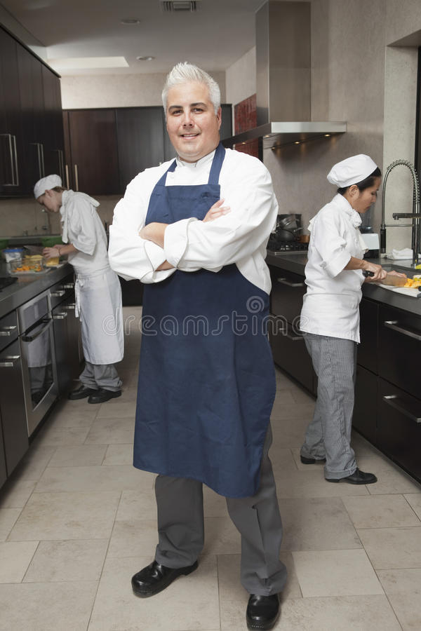 Confident Male Chef With Colleagues Working In Kitchen stock photos