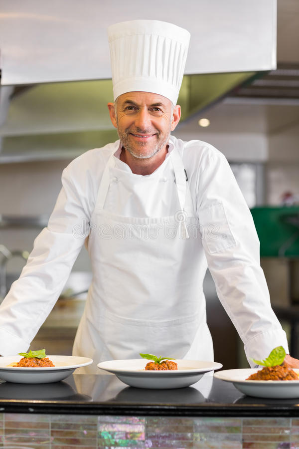 Confident male chef with cooked food in kitchen. Portrait of a confident male chef with cooked food standing in the kitchen royalty free stock photos
