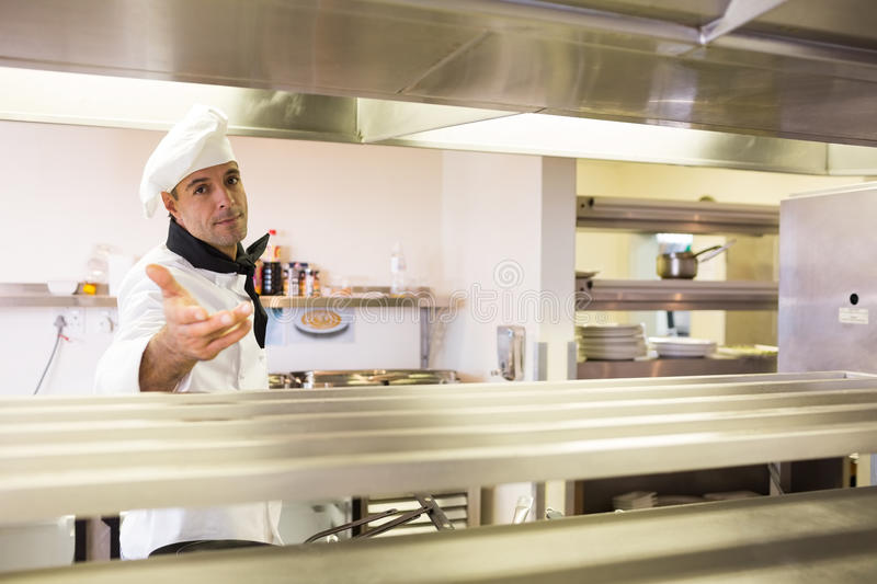 Confident male chef standing in kitchen. Portrait of a confident male chef standing in the kitchen royalty free stock photos