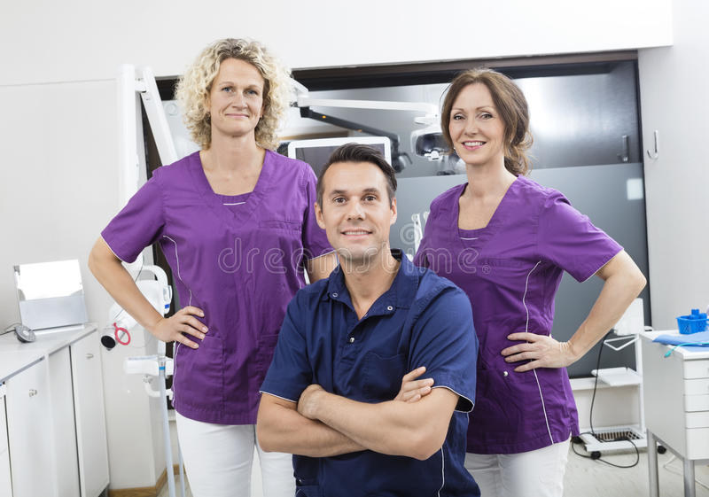 Confident Male Dentist With Female Assistants stock image