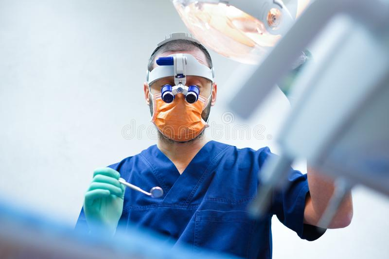 Dentist ready for a tooth surgical operation holding medical equipment royalty free stock photo
