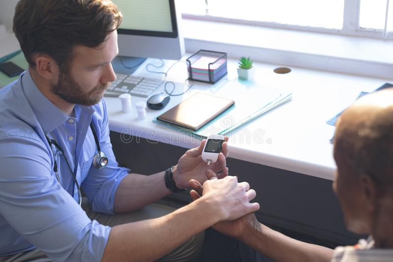 Confident male doctor examining senior man with glucometer in clinic stock photo