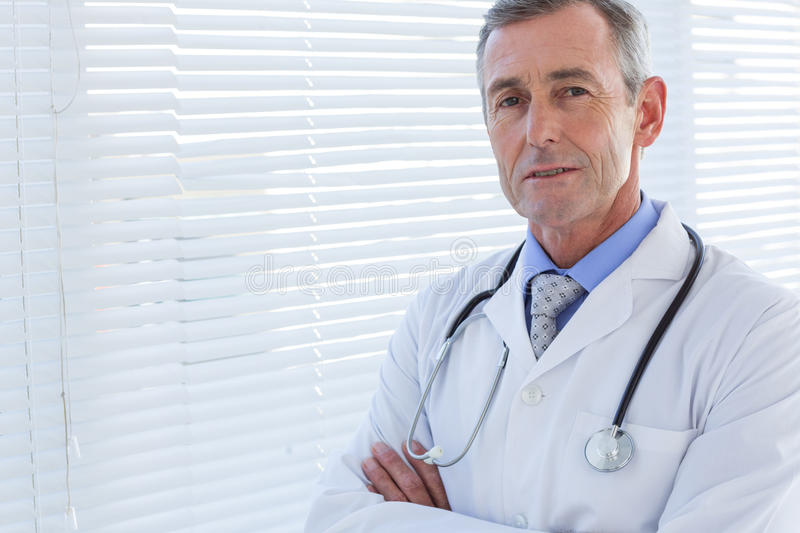 Confident male doctor looking at camera with arms crossed stock images