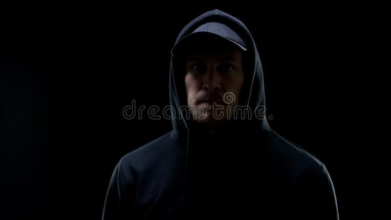 Confident male gangster in hoodie looking at camera against black background stock photo