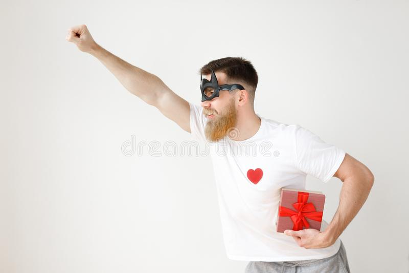 Confident male hero in batman mask, raises hand, hurries to help people, holds present box, going to give it someone stock image