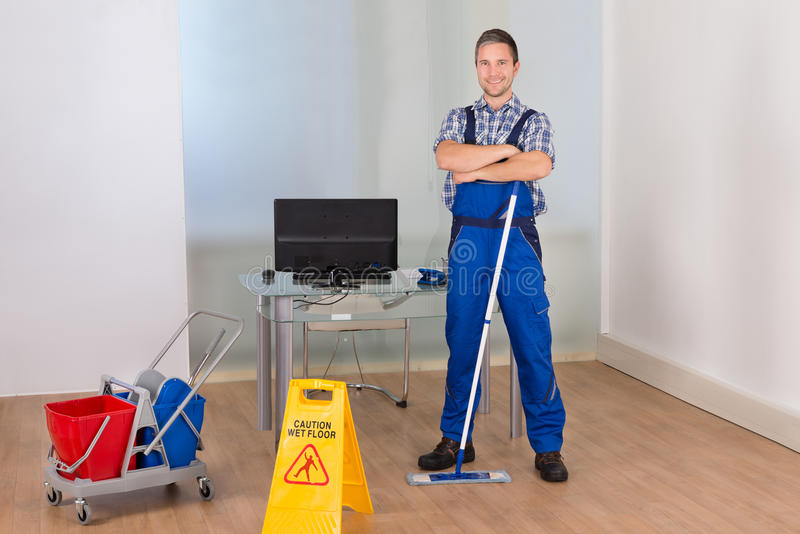 Confident male janitor with cleaning equipments stock image