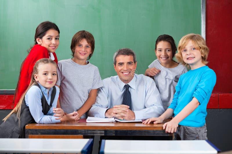 Confident Male Teacher With Schoolchildren At Desk stock photo