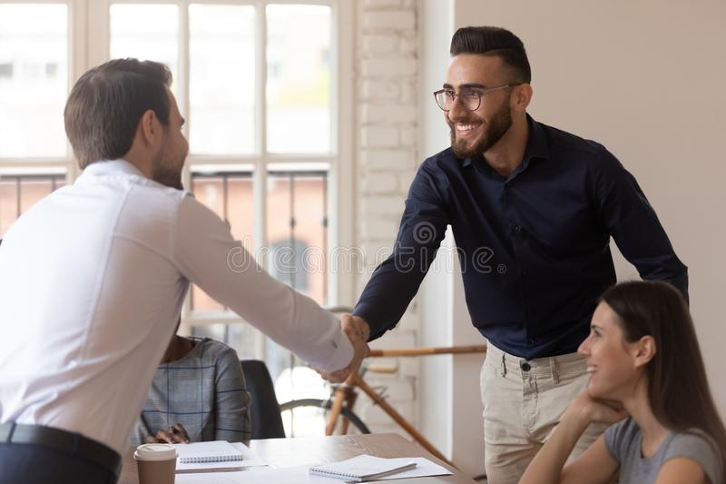 Confident male team leader shaking hands with young arabic employee. royalty free stock photo