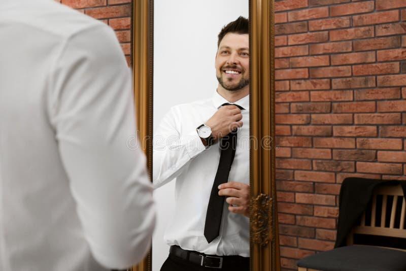 Confident man adjusting necktie near mirror royalty free stock photo