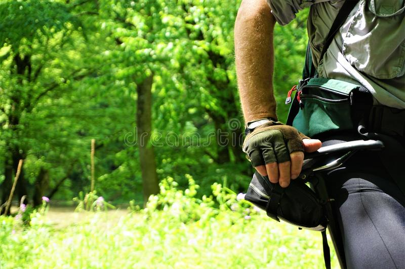 Confident man on bike resting hand on hip. Cyclist sits resting his palm on his hip and bags holding gear and equipment.  Shirtsleeves rolled up, bicycle stock photo