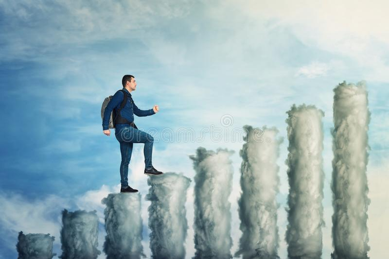Climb on graph. Confident man climb up to the top of a graph made of clouds over blue sky background. No limits growing success concept, business metaphor as stock images