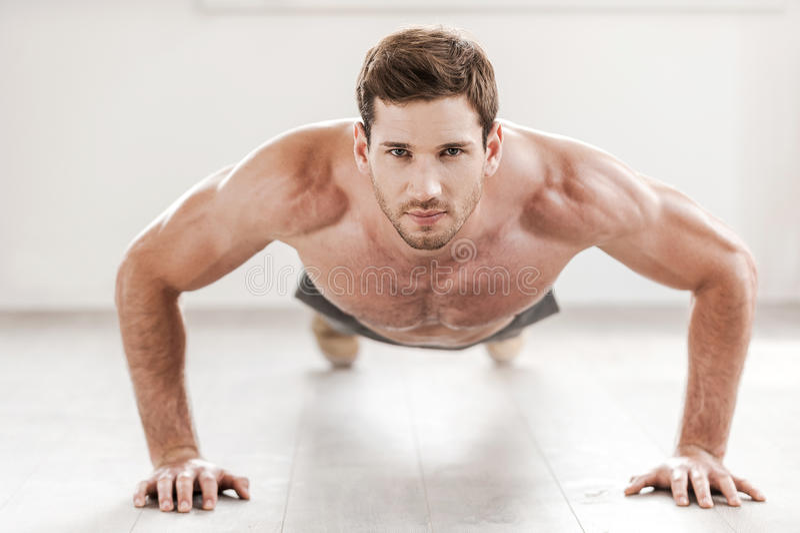 Confident man doing push-ups. stock photo