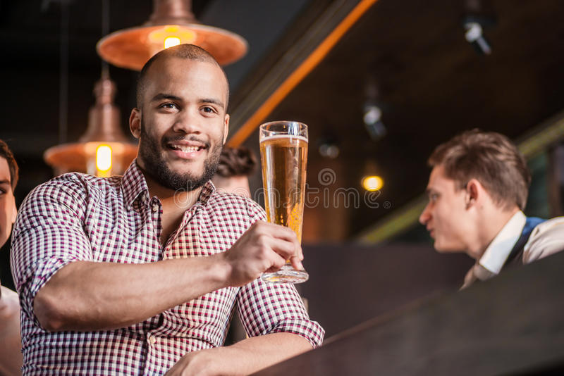 Confident man drinking beer at the bar. Man holds glass of beer royalty free stock images