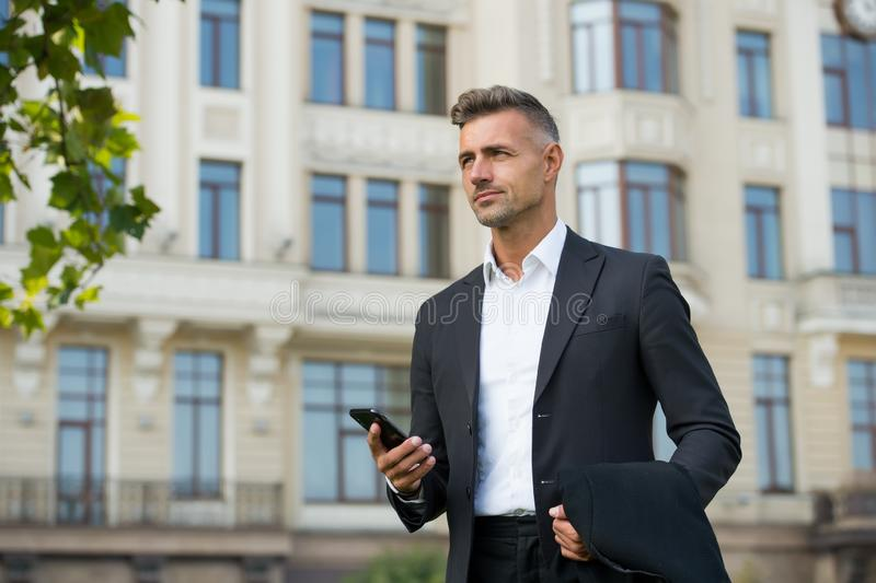 Confident man formal outfit. modern life concept. businessman on way to office. agile business. use phone while walking stock photo