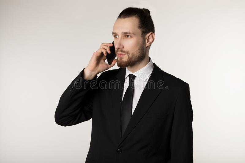 Confident man in formalwear with trendy beard and hairstyle holding a mobile phone royalty free stock images