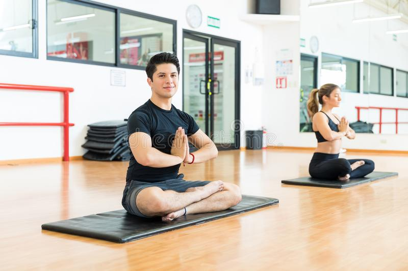 Confident Man With Hands Clasped Meditating With Friend In Gym royalty free stock photos