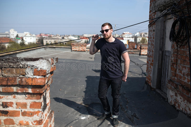 Confident man posing in selvedge jeans. The man in the authentic boots and jeans selvedge on the roof of the building in the old town royalty free stock image
