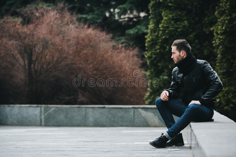 Confident man posing in selvedge jeans. A man dressed in jeans and black jacket seats on a slab royalty free stock photography