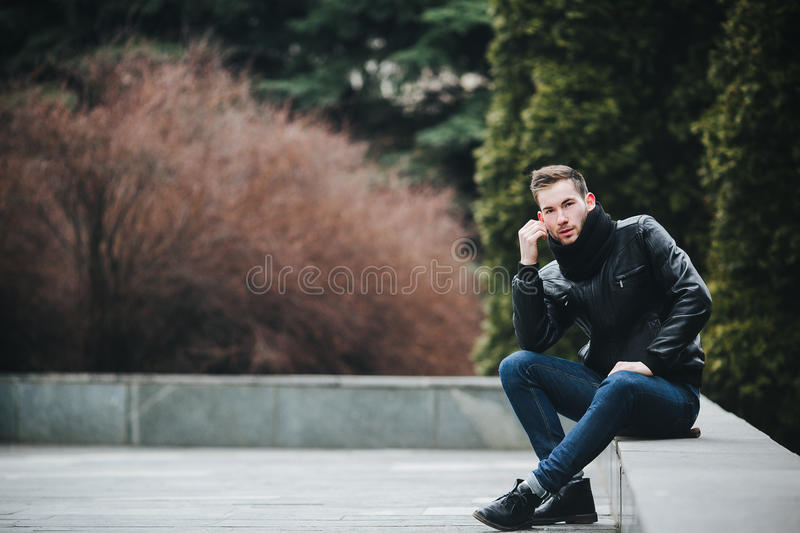 Confident man posing in selvedge jeans. A man dressed in jeans and black jacket seats on a slab royalty free stock photos