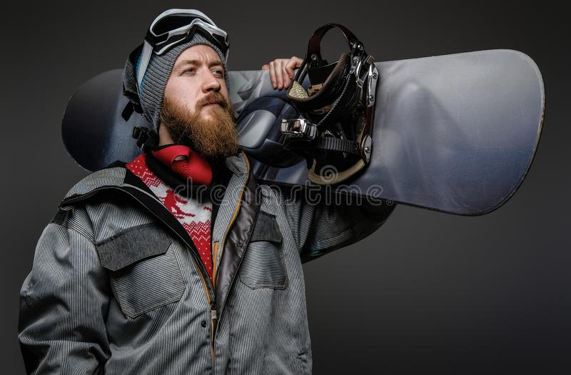 Confident man with red beard wearing a full equipment holding a snowboard on his shoulder, isolated on a dark background royalty free stock image