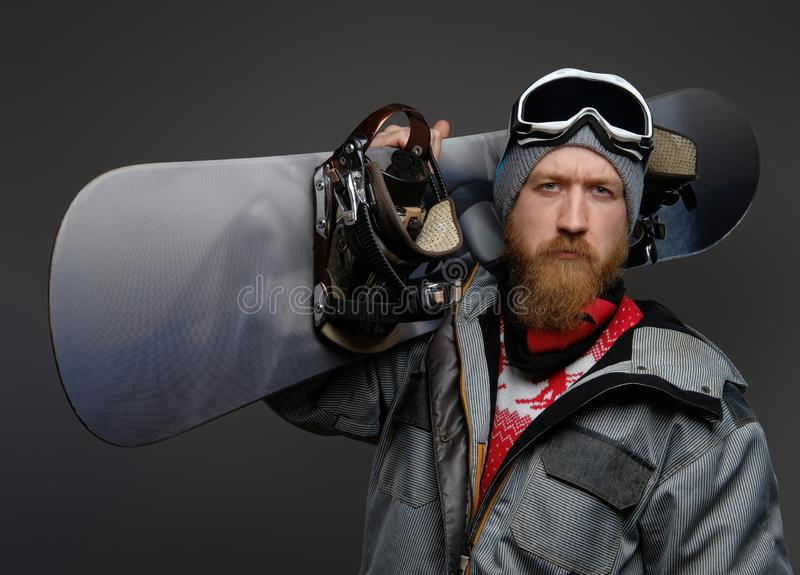 Confident man with a red beard wearing a full equipment holding a snowboard on his shoulder, looking at a camera with a royalty free stock photos