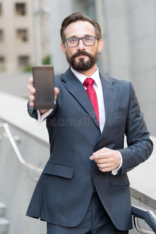 Confident man showing his smartphone while standing outdoors. Calm attractive bearded man standing alone in his dark suit and looking at you while showing the stock image