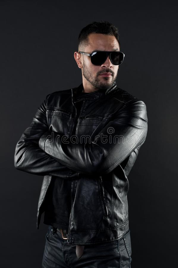 Confident man stand with arms folded. Bearded man in trendy sunglasses. Fashion model in leather jacket and jeans. Fashion and style. Confidence with sexuality royalty free stock images