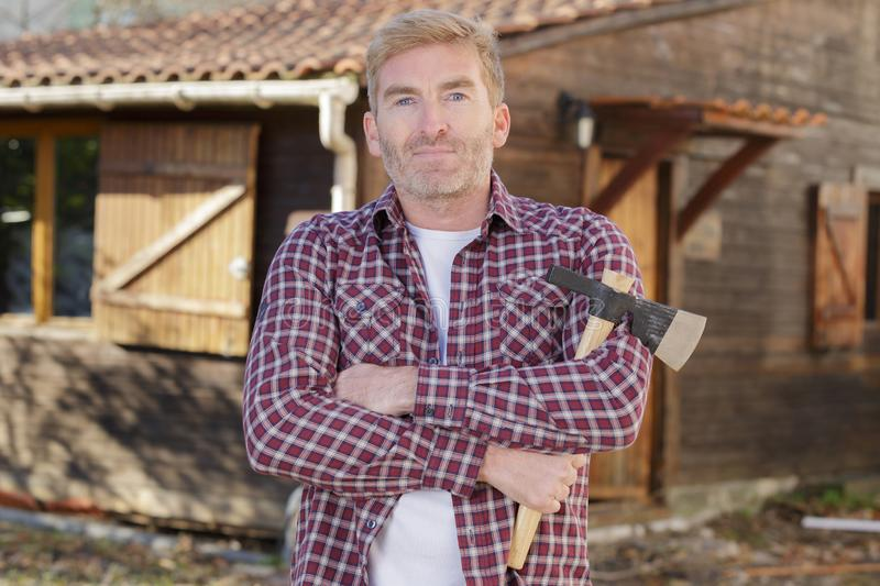 Confident man standing with axe outdoors. Man stock images