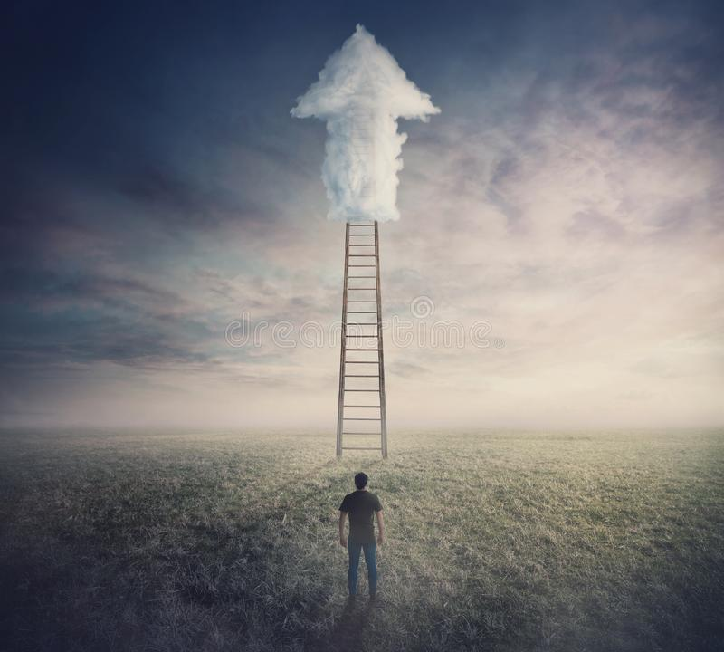 Confident man standing in front of ladder going up to the sky reaching an arrow shaped cloud. Stairway to heaven concept. Business stock photography