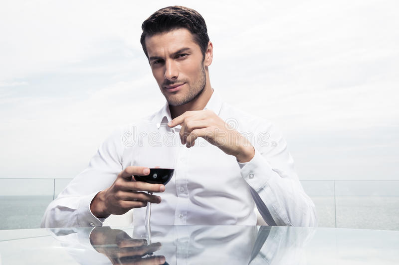Confident man standing with glass of wine royalty free stock photo