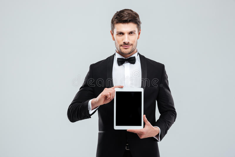 Confident man in tuxedo standing and holding blank screen tablet. Confident young man in tuxedo standing and holding blank screen tablet royalty free stock photo