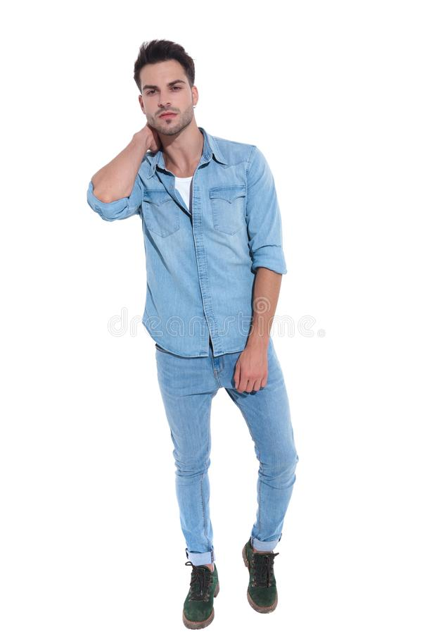 Confident man dressed in denim posing with hand behind neck stock image
