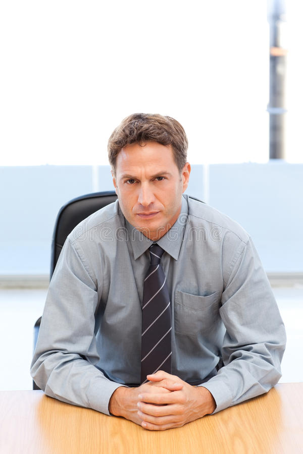 Confident manager posing alone at a table stock photo