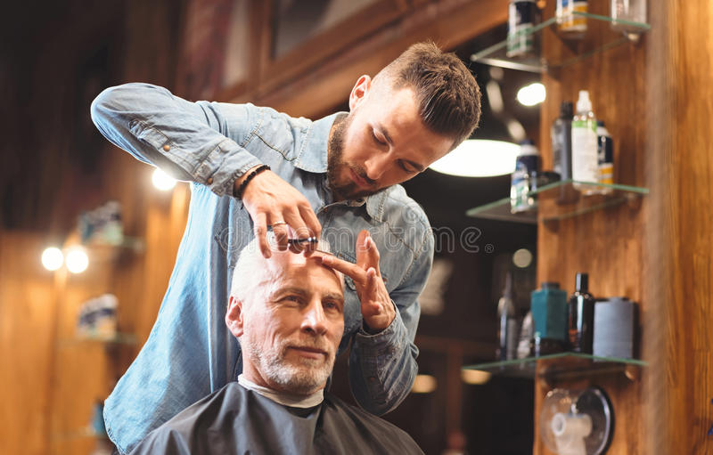 Confident master styling hairdo of the client in the barbershop. Styling brutal beauty . Bearded concentrated young hairdresser standing in the barbershop and stock images