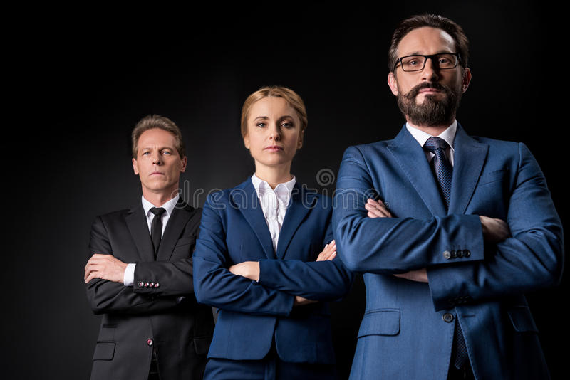 Confident mature business people standing with crossed arms and looking at camera stock photography