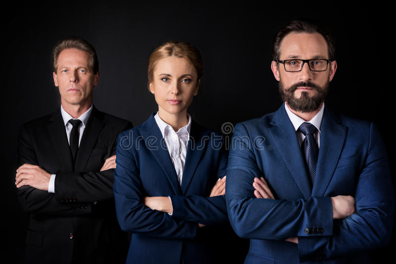 Confident mature business people standing with crossed arms and looking at camera royalty free stock photography