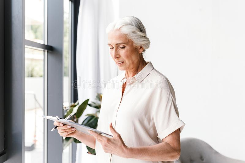Confident mature business woman taking notes royalty free stock images